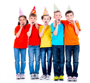 Group of happy children in colored t-shirts with party blowers - isolated on a white background.