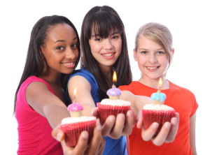 Birthday celebration with cakes for three beautiful young teenager girl friends a blonde caucasian, an oriental Japanese and an African American all with happy smiles.